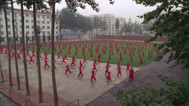 high angle down of men, teachers and boys, students, in courtyard or park practicing martial arts. could be kung fu. high rise apartment buildings in bg. - martial arts stock videos & royalty-free footage