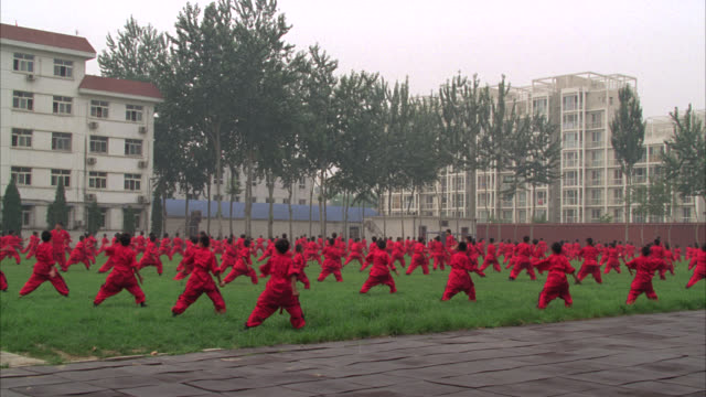pan right to left of men, teachers and boys, students, in courtyard or park practicing martial arts. could be kung fu. high rise apartment buildings in bg. - martial arts stock videos & royalty-free footage
