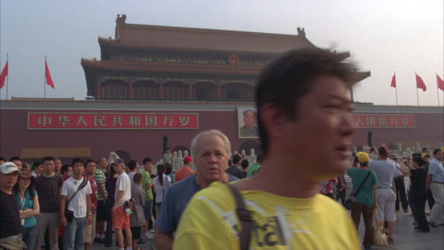 HAND HELD OF TIANANMEN GATE TO FORBIDDEN CITY. COULD BE TEMPLE, PALACE, GOVERNMENT OR IMPERIAL BUILDING. CHINESE PAGODAS. CROWD OF PEOPLE, PEDESTRIANS OR TOURISTS OUTSIDE.