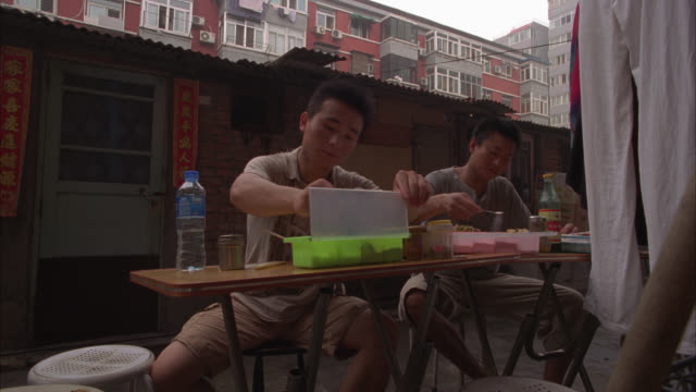medium angle of two men eating food at tables set up in alley behind lower class one story brick house. multi-story apartment buildings in bg. urban area. - brick house stock videos & royalty-free footage