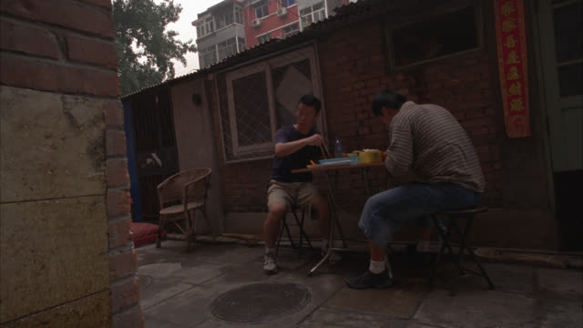 medium angle of two men eating food at tables set up in alley behind lower class one story brick house. multi-story apartment buildings in bg. urban area. they look at something. reactions. - brick house stock videos & royalty-free footage