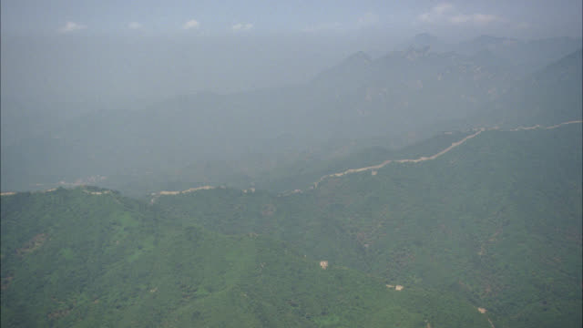 AERIAL OF GREAT WALL OF CHINA. FORTIFICATIONS. TREES AND FORESTS SURROUND WALL. ASIA. MOUNTAINS. TEMPLE ATOP MOUNTAIN. LANDMARKS.