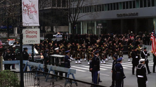 high angle down of funeral procession, police motorcycles and car. military soldiers marching with flags. bagpipe players. hearse. park avenue, midtown manhattan. city street. could be for military or government official. - hearse stock videos & royalty-free footage