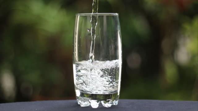 vidéos et rushes de pouring water in glass - en verre