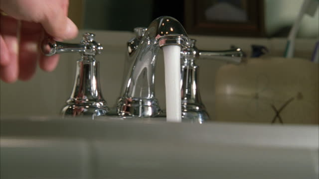 close angle of hand turning faucet on and off in bathroom. sink and water visible. soap dispenser and toothbrush holder with toothbrushes visible. mirror in bg. - toothbrush stock videos & royalty-free footage
