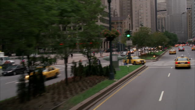 stockvideo's en b-roll-footage met wide angle driving pov of park avenue. cars and taxi cabs. midtown manhattan. city streets. people or pedestrians on sidewalk. skyscrapers or high rise office or apartment buildings. metlife building in bg. - metlife building