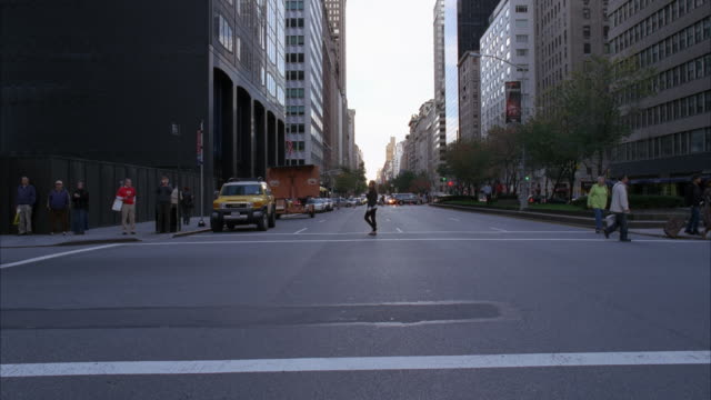 PROCESS PLATE STRAIGHT BACK DRIVING ON PARK AVENUE CITY STREET THROUGH MIDTOWN MANHATTAN. PEOPLE OR PEDESTRIANS CROSSING STREET. SKYSCRAPERS OR HIGH RISE OFFICE OR APARTMENT BUILDINGS LINING STREET. CAR SWERVING, COULD BE PART OF CAR CHASE.