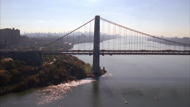 aerial of george washington bridge spanning new york and new jersey across hudson river. woods visible in bg. cars and trucks drive across bridge. barges and boats on river. camera zooms in to red toyota prius driving from manhattan towards new jersey. - hudson river stock videos & royalty-free footage