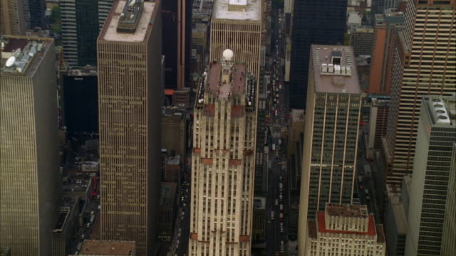 aerial of new york city skyline. high rises, skyscrapers, and office buildings visible. cities. camera zooms in to g.e. building. rockefeller center. office buildings. people visible standing on rooftop. could be observation deck. - rockefeller center video stock e b–roll