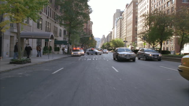 process plate straight back driving on city street through midtown manhattan. cars and taxis. people or pedestrians on sidewalk. multi-story or high rise brick apartment buildings. one-way street. police cars with flashing lights. - moving process plate stock videos & royalty-free footage