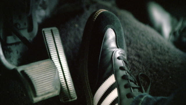 close angle of man's foot with sneaker pressing on accelerator or gas pedal. series. adidas sneaker. - pedal stock videos & royalty-free footage