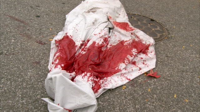 stockvideo's en b-roll-footage met close angle of body bag covered in blood or body wrapped in sheet on street. red toyota prius car runs over body. leg becomes exposed. - toyota motor