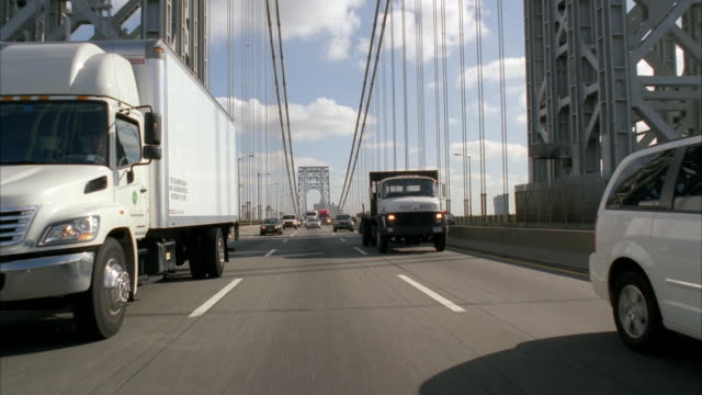 process plate straight back of cars and trucks driving across bridge. george washington bridge. traffic. river below bridge. city visible in bg. could be brooklyn. cars exit bridge. autumn trees. office buildings and tollbooth visible. - moving process plate stock videos & royalty-free footage