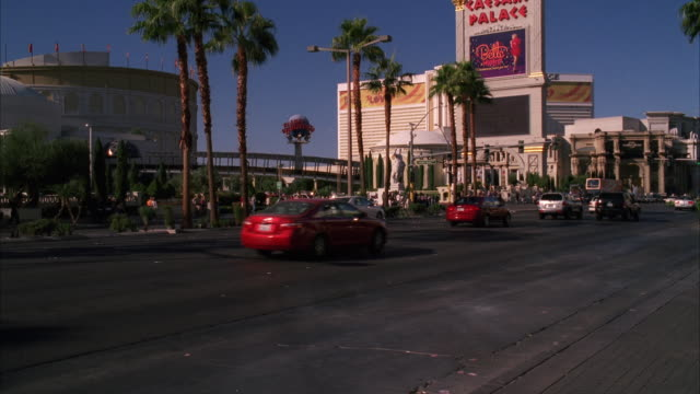 vídeos de stock, filmes e b-roll de wide angle of cars and traffic driving on las vegas strip. city street in front of caesar's palace hotel and casinos. signs visible. palm trees. - grande angular