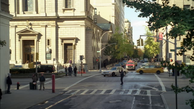 vidéos et rushes de pan down to red toyota prius driving on city streets, turning right off of park avenue onto side street. cars going through intersection. multi-story or high rise stone or concrete buildings. people or pedestrians in crosswalks. - turning on or off