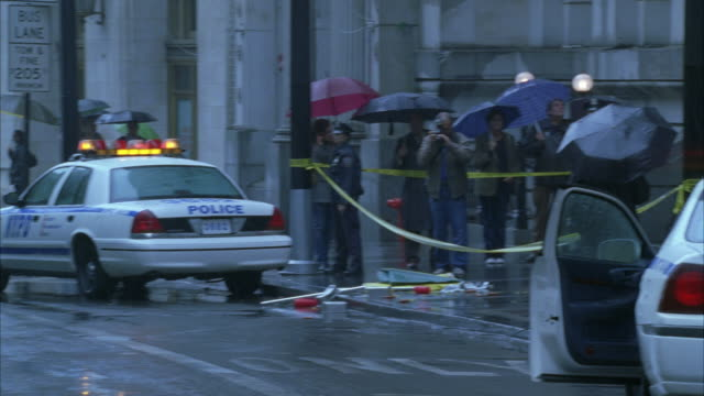 medium angle of crime scene in front of bank in city. people stand outside bank with umbrellas. rain. police tape visible. police car in fg with flashing light or bizbar. police officers visible. could be robbery. reporters visible. - crime stock videos and b-roll footage