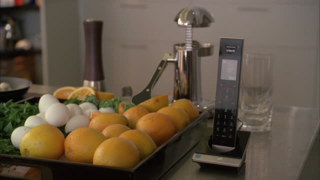 vidéos et rushes de zoom in on kitchen counter with oranges and eggs, juicer, and frying pan. camera zooms in on wireless phone. upper class. man's hand removes phone from holder. - stéréotype de la classe supérieure