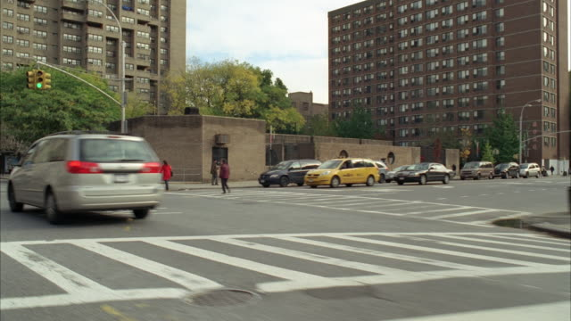 tracking shot driving 3/4 left back on city street, lower east side manhattan, new york city. high rise apartment buildings, trucks, cars, people or pedestrians, crosswalks, trees visible. urban area. - dolly shot stock videos & royalty-free footage