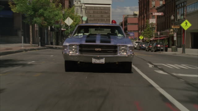 vídeos y material grabado en eventos de stock de high angle down moving pov of 1971 chevrolet chevelle driving through city streets with flashing bulb on roof. gun shots hit hood of car and send it flying upward towards windshield. sparks. could be car chase. car stunts. - sparks
