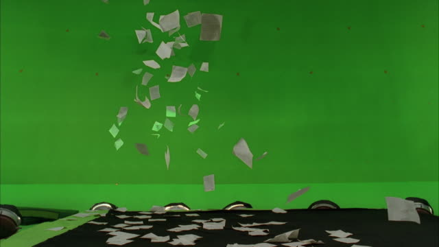 wide angle of papers flying through air against green screen background. could be parade confetti. - carta video stock e b–roll