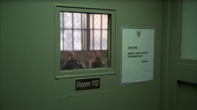 """medium angle of door and window. sign on door reads """"room 112 grief and relief counseling nypd."""" could be police station. men out of focus inside room in bg. - police station stock videos & royalty-free footage"""
