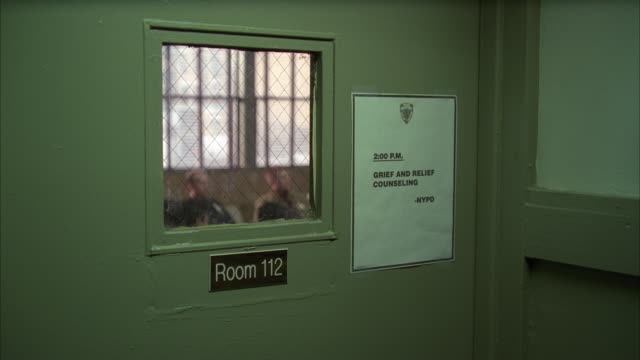 "medium angle of door and window. sign on door reads ""room 112 grief and relief counseling nypd."" could be police station. men out of focus inside room in bg. - police station stock videos & royalty-free footage"