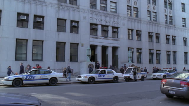 stockvideo's en b-roll-footage met wide angle of police station or headquarter in multi-story building. nypd police cars visible on city street. police officers and pedestrians on sidewalk. - hoofdkantoor