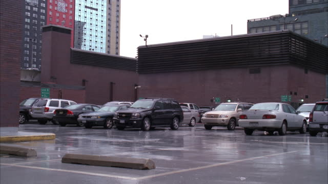 wide angle of rooftop parking lot or garage. cars visible. rain slicked pavement. high rise office or apartment buildings visible in bg. person in all black riding motorcycle crashes into parked red volkswagen car. stunts. - volkswagen stock-videos und b-roll-filmmaterial