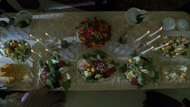 high angle down over dining room table set with food, flowers, and candles. could be dinner, party, or funeral. cheese, meat, and fruit plates visible. - dining table stock videos and b-roll footage