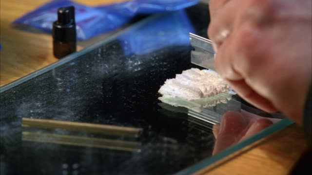 close angle of man's hand cutting cocaine powder with razor blade on mirror. drugs. - cocaina video stock e b–roll