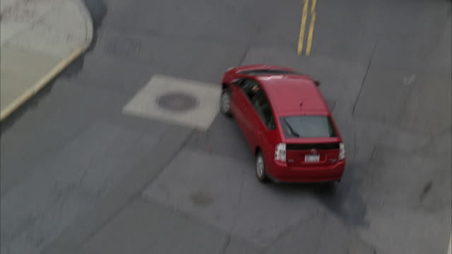 stockvideo's en b-roll-footage met high angle down of red toyota prius swerving between two white vans blocking city street. could be escape. car chase. car stunt. near collision. - toyota motor