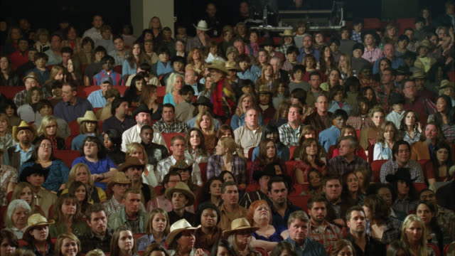 wide angle of crowd of people cheering and clapping. applause. could be in stadium or theater. could be at country music concert. spectators or audience. cowboy hats. - cheering stock videos & royalty-free footage