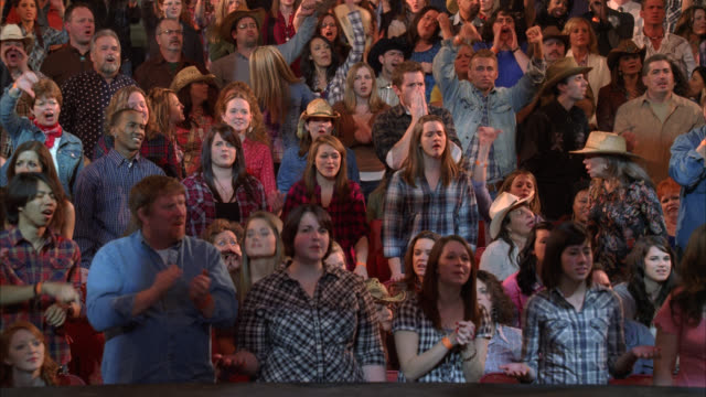 medium angle of people, crowd, spectators, audience in theater, stadium or auditorium. clapping, applause, cheering. could be at country music concert. cowboy hats. - country music stock videos and b-roll footage
