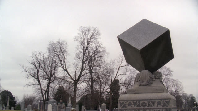 wide angle of stone cube statue, gravestone or memorial. graveyard, cemetery. bare branches on trees. overcast sky. - tennessee stock videos & royalty-free footage