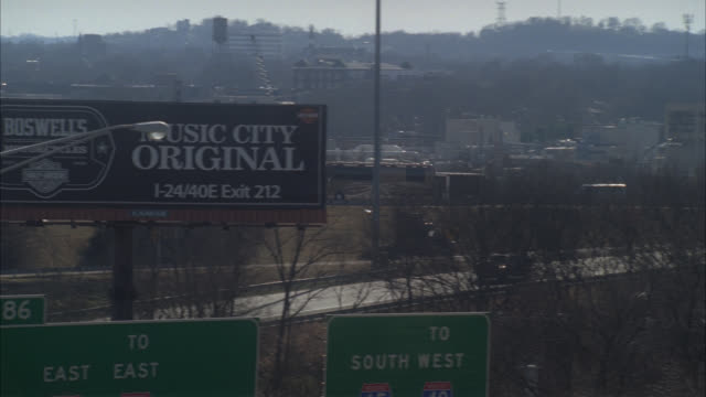 pan right to left of tour bus and vans traveling right to left on freeway or highway outside of nashville. advertisement or billboard and freeway exit sign visible in fg. cars driving on freeway. - tennessee stock videos & royalty-free footage