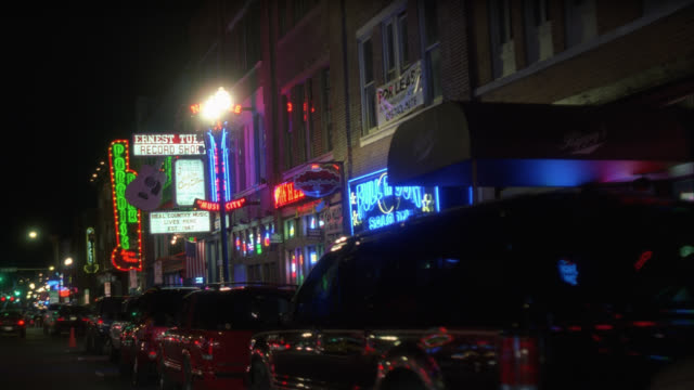 process plate 3/4 back right of downtown nashville. cars parked on curb outside bars, restaurants, and shops. neon signs and lights. urban area. pedestrians visible. - tennessee stock videos & royalty-free footage