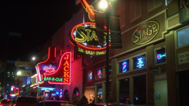 process plate 3/4 back right of downtown nashville. cars parked on curb outside bars, restaurants, and shops. neon signs and lights. urban area. pedestrians visible. - nashville stock videos & royalty-free footage