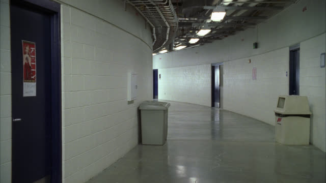 wide angle of backstage hallway of concert venue or sport's arena. cinderblock walls. poster on door. trash cans and recycle bins in hallway. man walks down hallway. - backstage stock videos & royalty-free footage