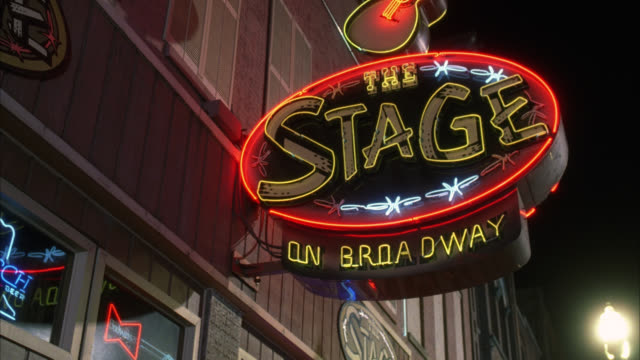 pan down from neon sign for the stage on broadway. bar or nightclub. - nashville stock videos & royalty-free footage