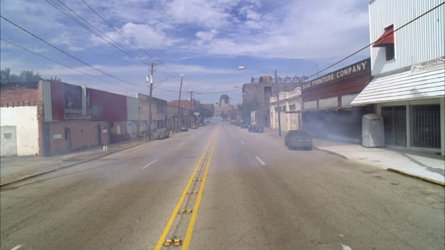 stockvideo's en b-roll-footage met wide angle moving pov of lower class suburbs or rural area street lined with abandoned or rundown buildings and restaurants. smoke visible lingering on street. - {{ collectponotification.cta }}