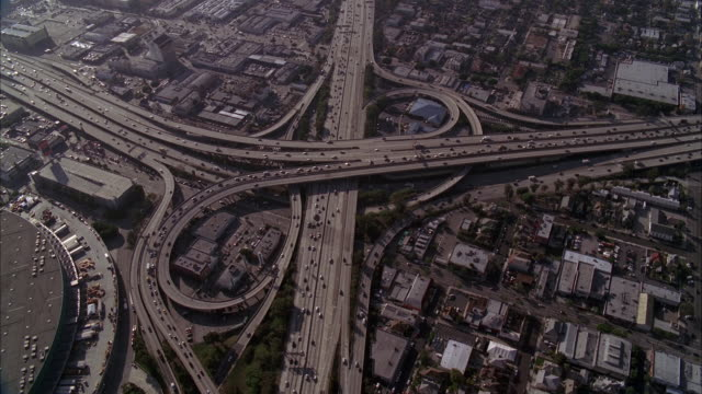 AERIAL OVER LOS ANGELES 110 FREEWAY AND CONVENTION CENTER. CARS DRIVING OF FREEWAY OR HIGHWAY. CITIES. CAMERA PANS UP TO LOS ANGELES CITY SKYLINE. HIGH RISES AND SKYSCRAPERS VISIBLE. OFFICE BUILDINGS. DOWNTOWNS.