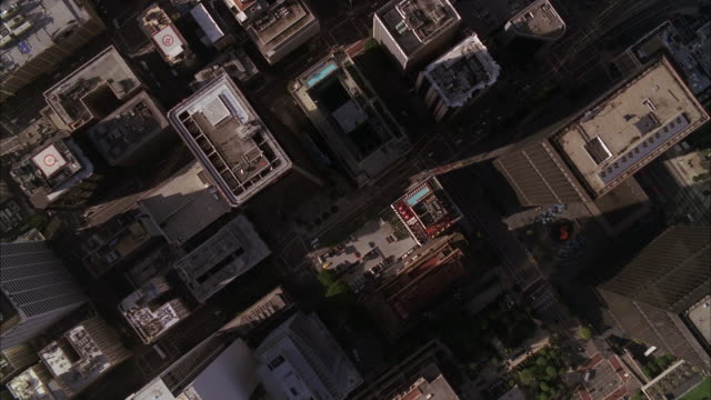 stockvideo's en b-roll-footage met aerial over roofs of buildings of los angeles city skyline. high rises and skyscrapers visible. office buildings. downtowns. us bank tower. - us bank tower