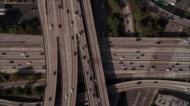 AERIAL OVER LOS ANGELES 110 FREEWAY. CARS DRIVING OF FREEWAY OR HIGHWAY. CITIES. CAMERA PANS UP TO LOS ANGELES CITY SKYLINE. CAMERA FACES SOUTH TOWARDS LONG BEACH AND AIRPORT.