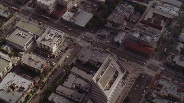 stockvideo's en b-roll-footage met aerial over urban area or city. cars driving on city streets. office buildings, apartment buildings, shops, and restaurants. camera pans up to los angeles city skyline in bg. - {{ collectponotification.cta }}