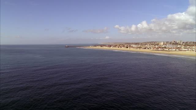 vídeos y material grabado en eventos de stock de aerial of pacific coast. beach and shore visible. could be long beach area. beach houses, marinas, and coast visible. small pier visible. - long beach los ángeles