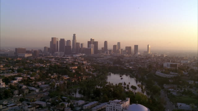 stockvideo's en b-roll-footage met aerial of los angeles downtown skyline from silverlake reservoir. high rises office buildings and skyscrapers. us bank tower visible. apartment buildings visible. palm trees and trees near reservoir. could be park. - us bank tower