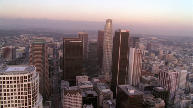 stockvideo's en b-roll-footage met aerial over downtown los angeles skyline. high rise buildings and skyscrapers visible. us bank tower. sunset. mountains visible in bg. - us bank tower