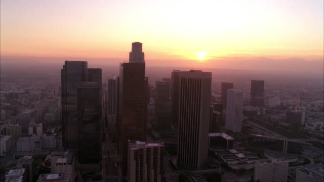 stockvideo's en b-roll-footage met aerial over downtown los angeles skyline. high rise buildings and skyscrapers visible. us bank tower. sunset. - us bank tower
