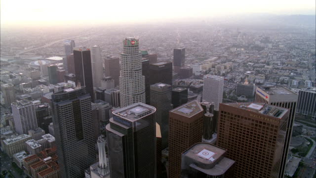 stockvideo's en b-roll-footage met aerial of downtown los angeles skyline. high rise buildings and skyscrapers visible. us bank tower. sunset. staples center and convention center visible. - us bank tower