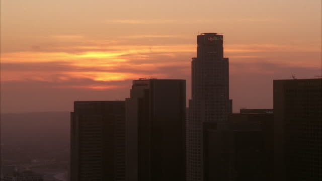 stockvideo's en b-roll-footage met aerial close angle of downtown los angeles skyline. high rise buildings and skyscrapers visible. us bank tower. sunset. - us bank tower